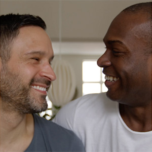 Two gay men smiling at each other.