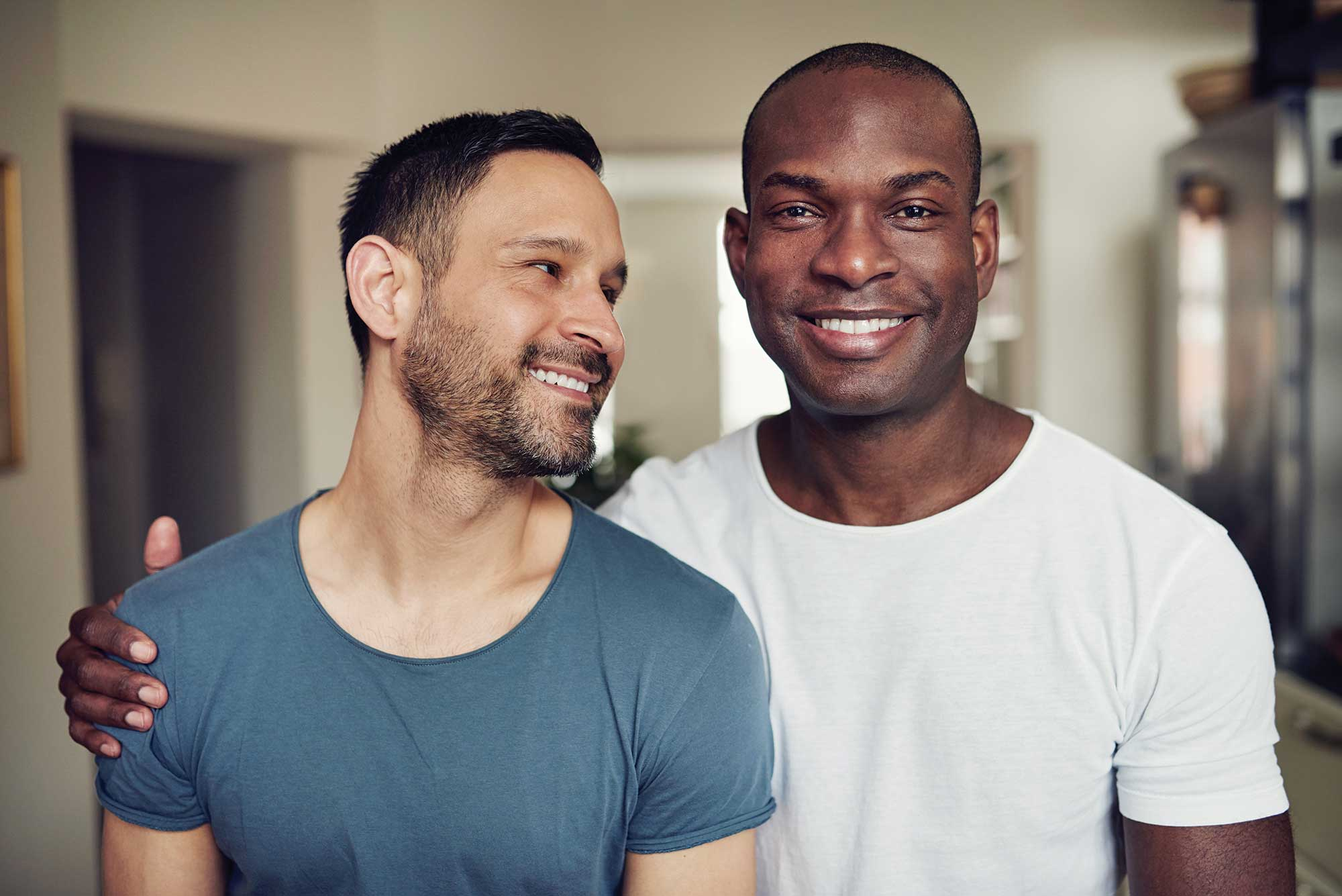 Gay Male couple looking at each other, looking at the camera