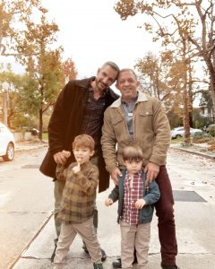 Two gay dads posing with their twins achieved through IVF and surrogacy