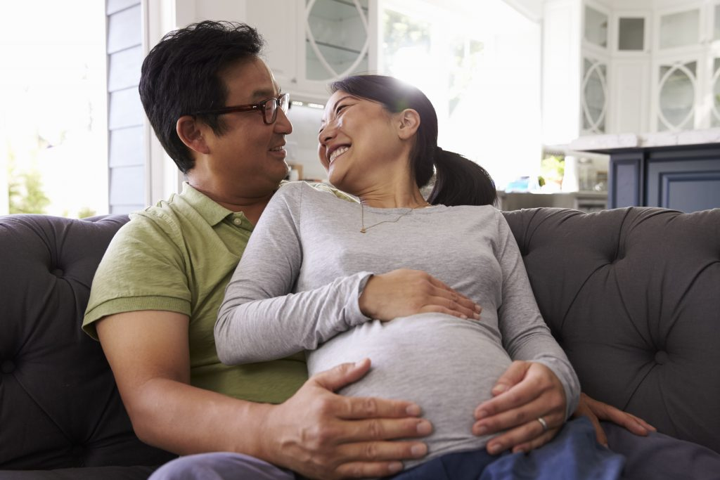 Expectant Couple Relaxing On Sofa At Home Together