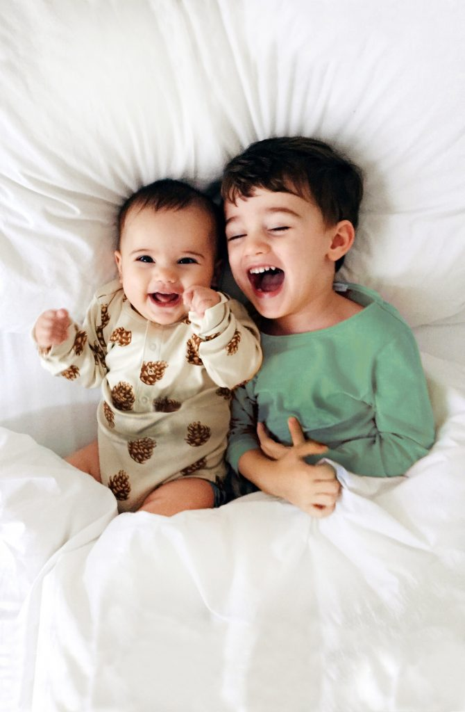 Two kids in a bed, baby laughing