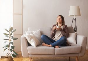 A woman sitting drinking coffee for self-care during the two-week-wait between ovulation and your pregnancy test.
